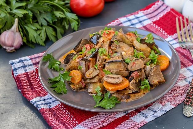 Serca z kurczaka gotowane z warzywami: marchewką, bakłażanem, pomidorami, czosnkiem i cebulą, na smaczny i zdrowy obiad, w orientacji poziomej