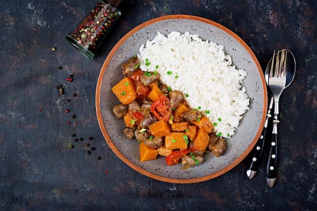 Serca z kurczaka z dynią i pomidorami w sosie pomidorowym. dekorację podaje się z gotowanym ryżem. leżał płasko. widok z góry.