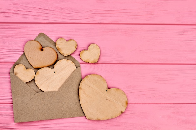 Serca ze sklejki, envlope i kopia przestrzeń. puste drewniane serca z otworem i kopertą na kolorowe tło drewniane, miejsca na tekst.