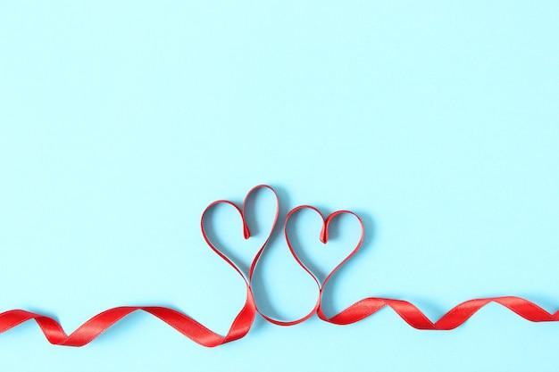 Serca ze wstążek na kolorowym tle widok z góry