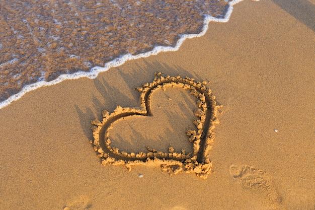 Serce czeka na piaszczystej plaży nad morzem.