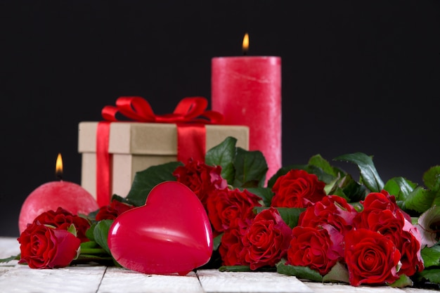 Serce i bukiet czerwonych róż z prezentem i świecami