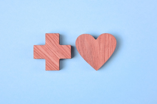 Serce i krzyż, drewniane ikony zabarwione różową plamą na bladoniebieskim tle