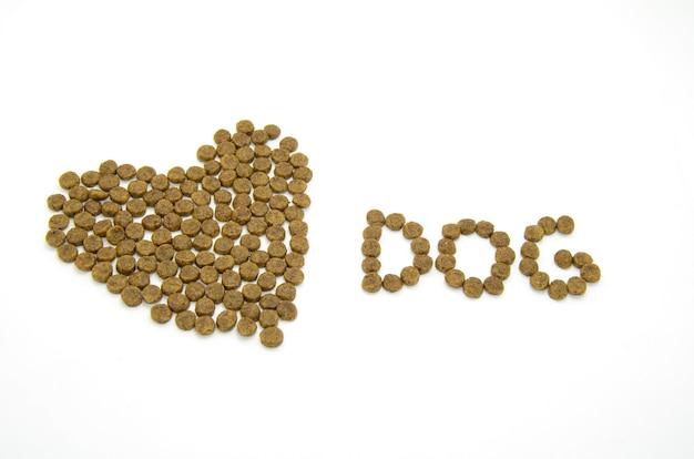 Serce i słowo dog pokryte suchą karmą dla zwierząt na białym tle