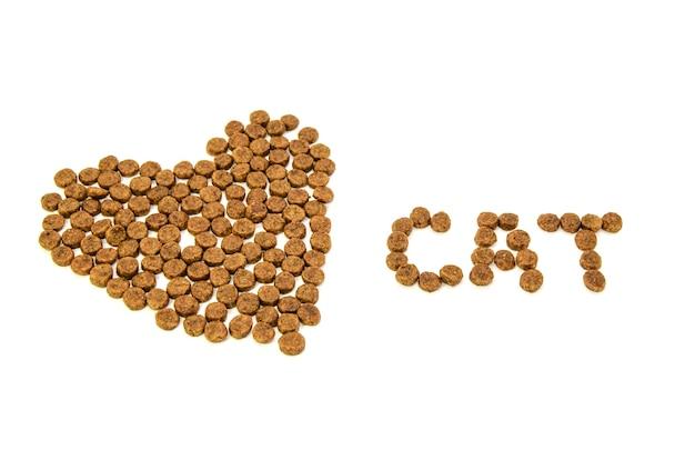 Serce i słowo kot pokryte suchą karmą dla zwierząt na białym tle