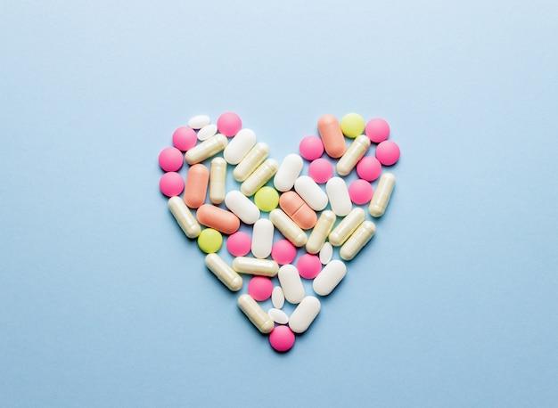 Serce jest ułożone z tabletek na niebieskim stole. zdrowie. medycyna. apteka.
