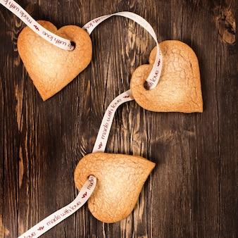 Serce kształtował imbirowych ciastka nad ciemnym drewnianym tłem