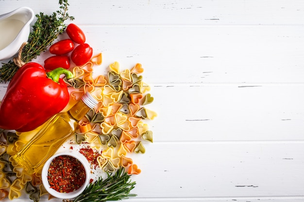 Serce kształtował makaron z składnikami na szarym tle, odgórny widok. makaron, śmietana, szpinak, pomidory i zioła.