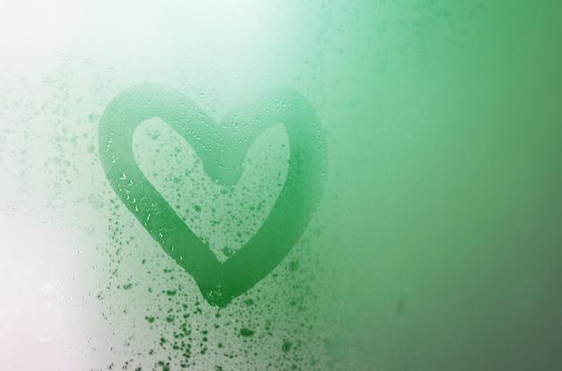 Serce maluje się na zaparowanym szkle zimą