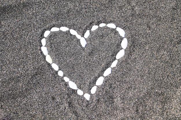 Serce muszli na nadmorskiej plaży na czarnym piasku. romantyczny tło.