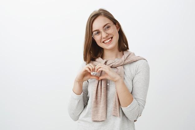Serce oznacza miłość. portret delikatnej uroczej kobiety z krótką brązową fryzurą przechylającą głowę delikatnie uśmiechnięta i wpatrzona w zakochanego chłopaka stojącego zadowolona, robiąca czarującą niespodziankę
