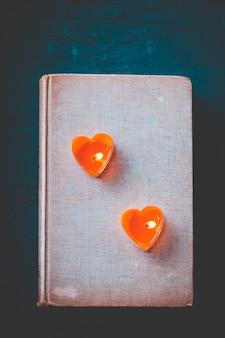 Serce pary to świece na starej książce, filtr vintage ciemny