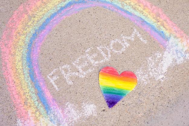 Serce pomalowane w barwach społeczności lgbt, napis wolność i tęcza narysowana kredą na asfalcie, symbol społeczności lgbt