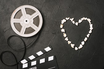 Serce popcorn w pobliżu filmu i clapperboard
