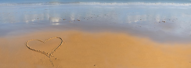 Serce rysunek na piasku nad brzegiem morza