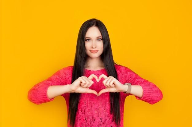 Serce składa się z rąk wykonanych przez dziewczynę na jasnożółtej ścianie w różowym swetrze. pomysł jest realizowany z miłością, dawaj miłość, emocje zaufania i współczucia