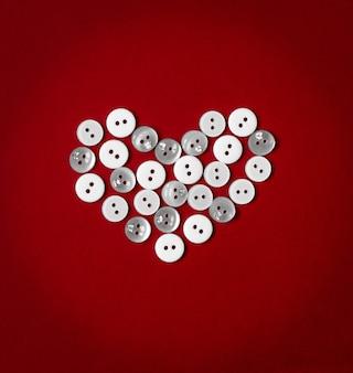Serce składa się z wielu białych przycisków na czerwonym tle.