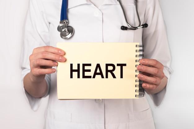Serce słowo na papierze w rękach lekarza, pojęcie medyczne.