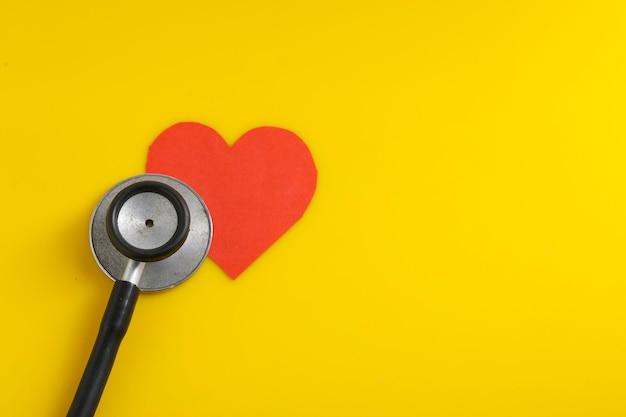 Serce stetoskopem na żółtym tle.