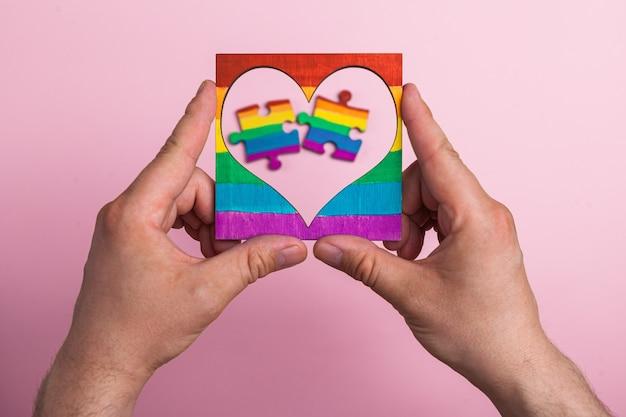 Serce w ramce z symbolem lgbt w męskich dłoniach wewnątrz układanki pomalowanej tęczą na masce medycznej.