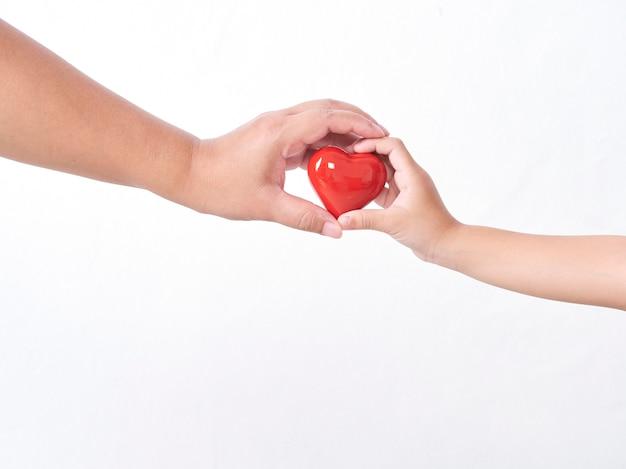Serce w rękach dziecka i matki na lekkiej ścianie. koncepcja dnia matki