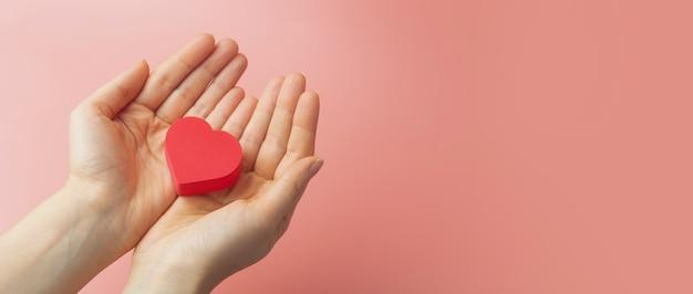 Serce w rękach kobiety na kolorowym tle. tło na walentynki (14 lutego) i miłość.