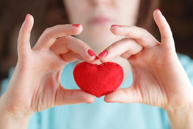 Serce w rękach kobiety trzyma ręcznie szyta miękka zabawka