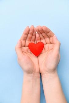 Serce w rękach na błękitnym tle. pojęcie walentynek i dnia kobiet. widok z góry, miejsce na tekst. życie