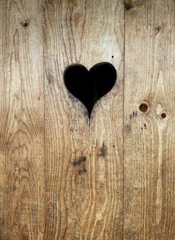 Serce wycięte z brązowych drewnianych drzwi toalety