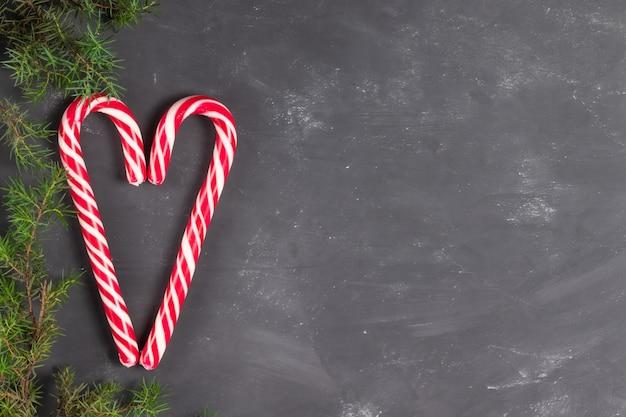 Serce wykonane z cukierków kije na tle kredy z gałęzi świerkowych kopia przestrzeń