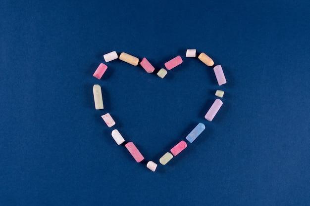 Serce wykonane z kredowych pastelowych kolorów na trendowym klasycznym niebieskim tle w kolorze 2020. koncepcja walentynki 14 lutego. leżał z płaskim, kopia przestrzeń, widok z góry, baner.