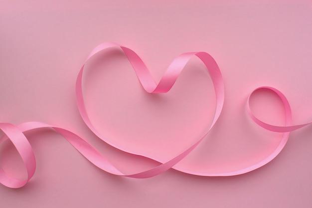 Serce wykonane z różowej wstążki na różowym tle