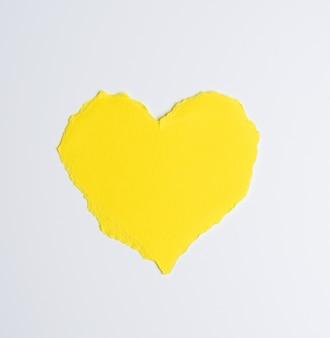 Serce wykonane z żółtego papieru na białym tle, z bliska