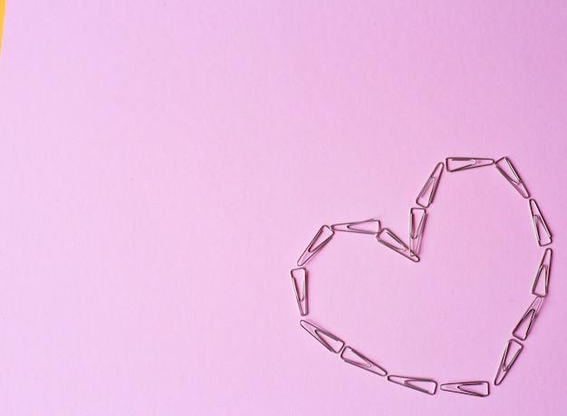 Serce wykonane ze spinaczy na różowym tle