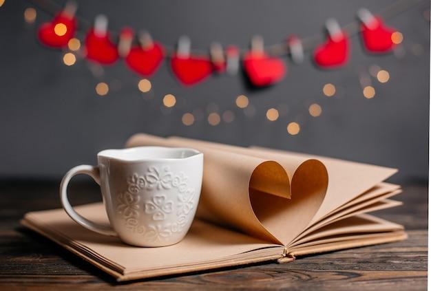 Serce z arkuszy książek z kubkiem w koncepcji światła, miłości i walentynek na drewnianym stole
