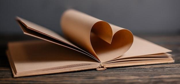 Serce z arkuszy książki, koncepcja miłości i walentynki na drewnianym stole