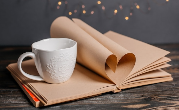 Serce z arkuszy książki z kubkiem w koncepcji światła, miłości i walentynek na drewnianym stole