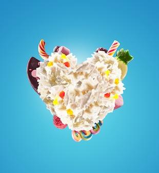 Serce z bitej śmietany ze słodyczami, galaretkami, widok z przodu serca. szalony trend jedzenia freakshake. serce z kremem, pełne słodyczy z jagodami i żelkami, koncepcja cukierków czekoladowych.