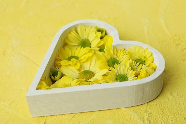 Serce z chryzantemami na żółtym tle z teksturą.