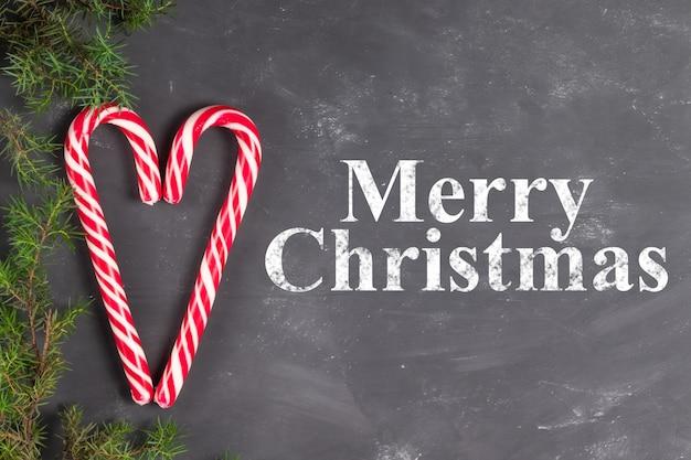 Serce z cukierków laski na tle kredy z gałęzi jodłowych z napisem wesołych świąt