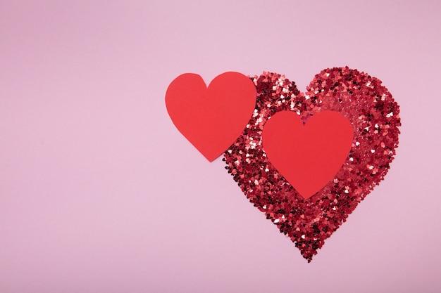Serce z czerwonego brokatu i dwa ręcznie robione serca na różowym tle. koncepcja miłości.