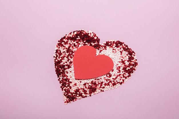 Serce z czerwonego brokatu oraz drugie ręcznie robione serce na różowym tle. koncepcja miłości