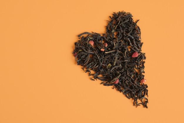 Serce z herbaty na białym tle na brązowym tle kopia przestrzeń widok z góry