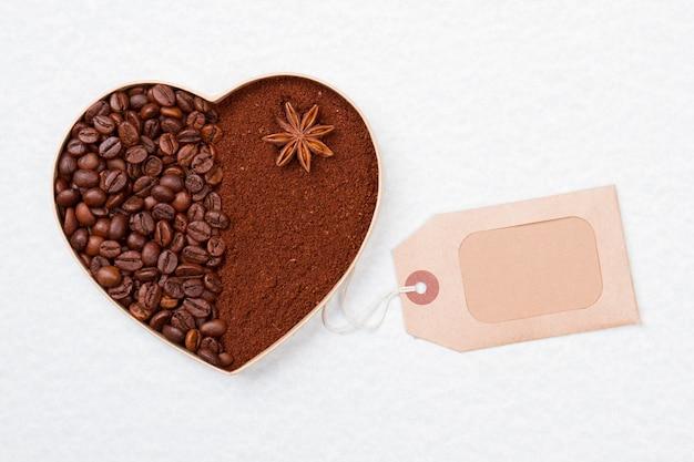 Serce z kawy rozpuszczalnej w proszku i ziaren. czysty papierowy znacznik. na białym tle na białej powierzchni