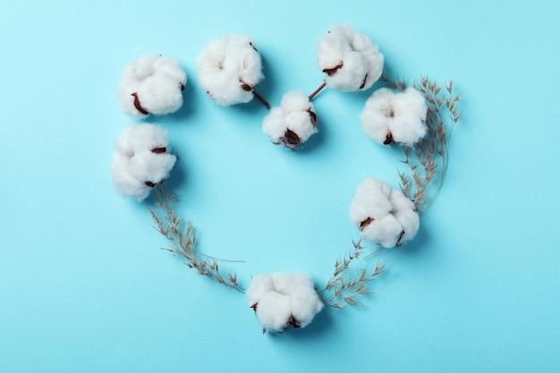 Serce z kwiatów roślin bawełny na niebieskiej powierzchni