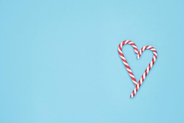 Serce z lasek cukierków na niebieskim tle. minimalna koncepcja miłości