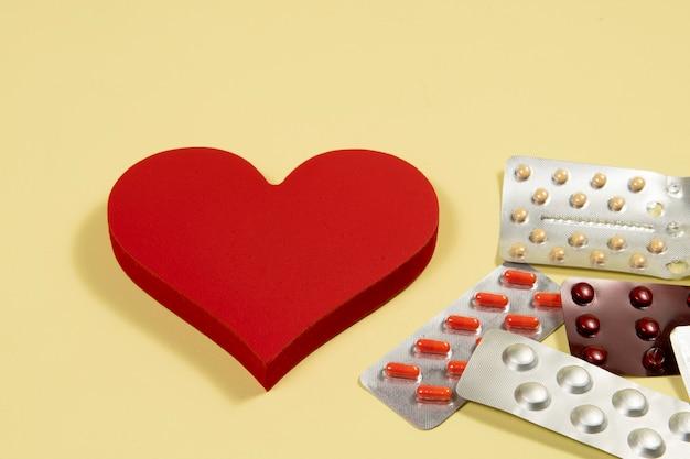 Serce z lekami na pęcherze symbolizujące leczenie ludzkiego narządu na żółtym tle