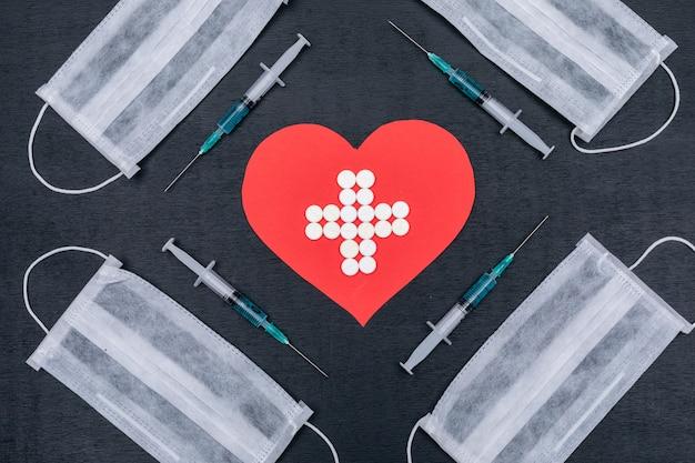 Serce z lekarstwami w środku ze strzykawkami i maskami ochronnymi