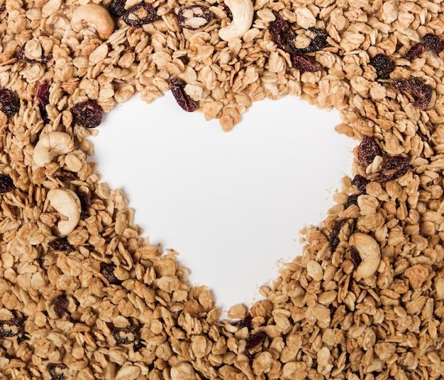 Serce z organicznej granoli z orzechami, żurawiną i rodzynkami na białym tle. tło