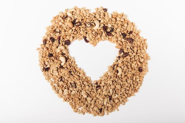 Serce z organicznej granoli z orzechami, żurawiną i rodzynkami na białym tle.
